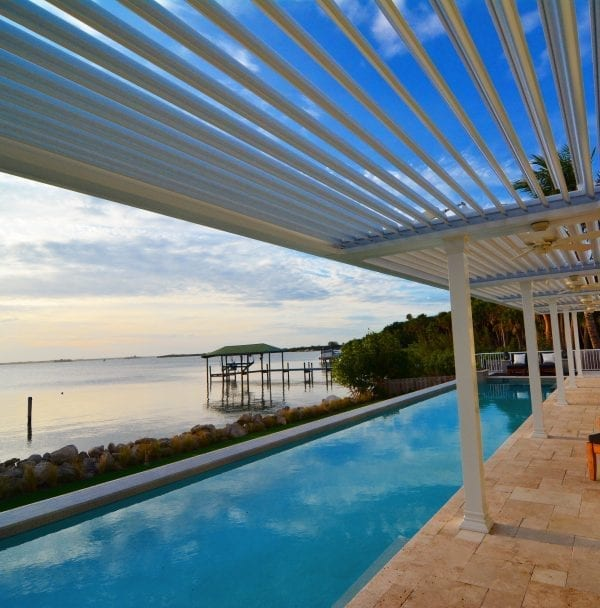 Under edge of white pergola with louvers opened next to turquoise lap pool with lake beyond