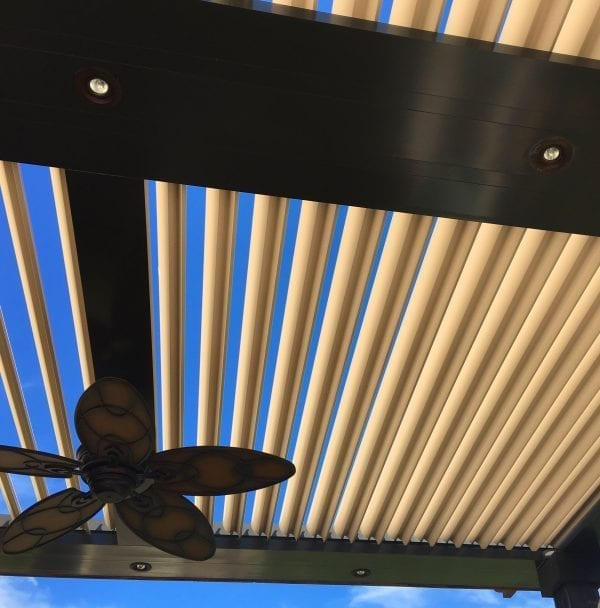 Close-up detail of black framed pergola with pivoting beige louvers with blue sky visible between opened louvers