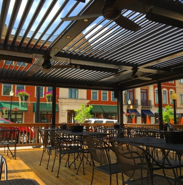Commercial wood deck with black iron furniture surrounded by wood railing underneath black pivoting louvered pergola system with colorful low-rise buildings in distance