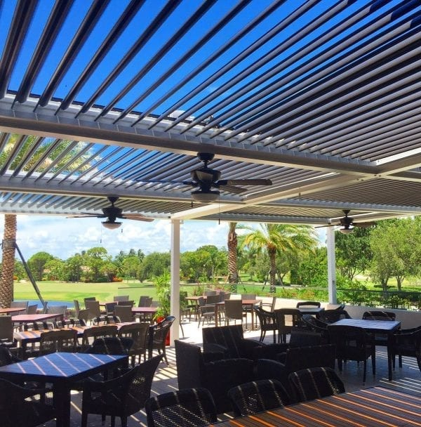 Commercial patio with dining tables of various sizes shaded by pivoting louvered pergola system with golf course and palm trees beyond