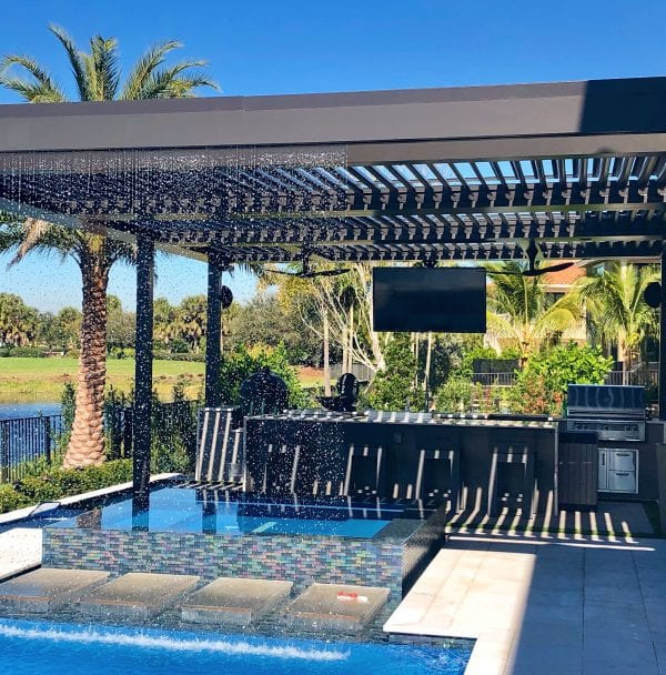 Rain feature at front of bronze pivoting louver pergola with pool and outdoor kitchen