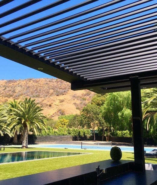 View from under dark colored pivoting louvered pergola looking across yard at pool and tennis court against palm tree and tan desert hillside