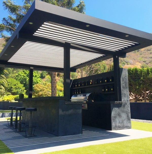 Stand-alone black and white pergola system attached by posts to black cement tequila bar with nature surrounding it