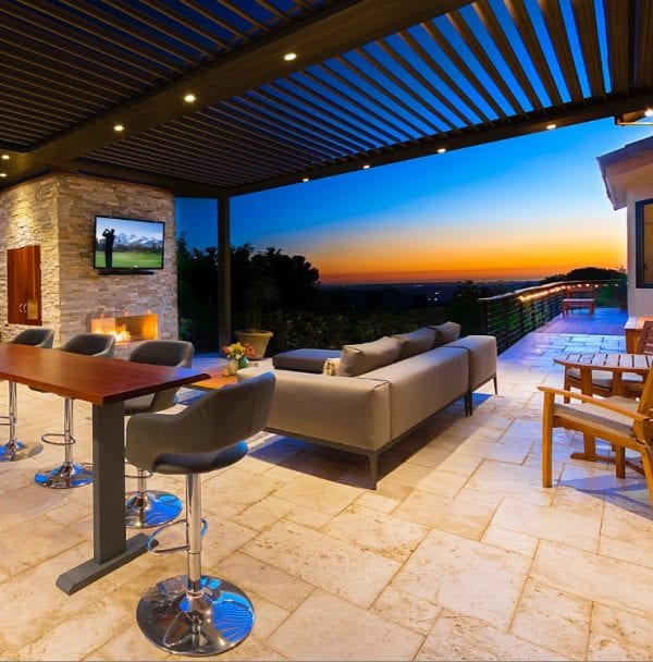 Deep blue yellow orange sunset seen through stone patio with luxury outdoor furniture and mounted flat screen TV all covered by louvered-roof pergola