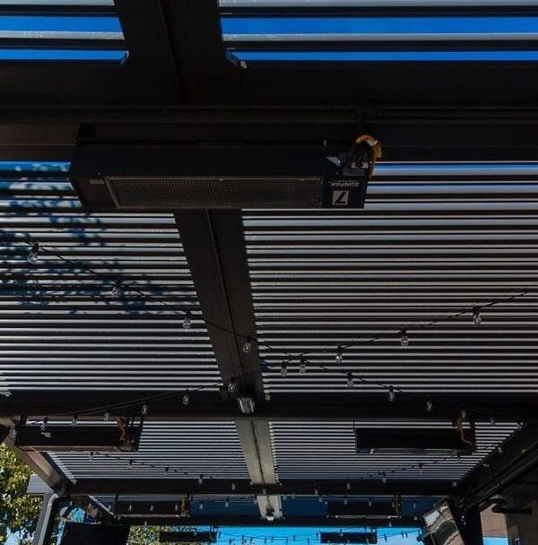 Close-up under view of opened bronze louvered pergola with turned off string lights criss-crossing underneath