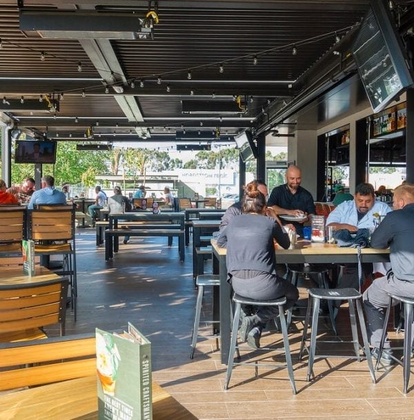 Outdoor restaurant seating area with people dining under dark adjustable louvered pergola with louvered closed on sunny day