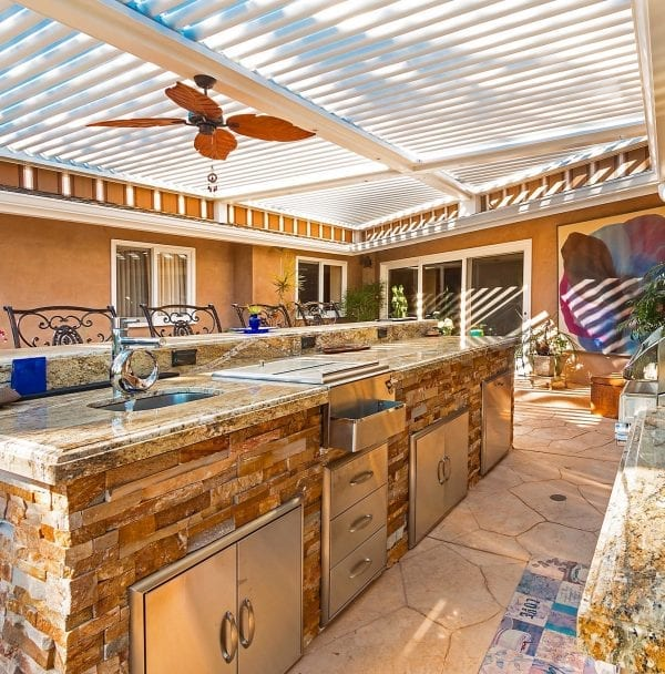 White pivoting louvered pergola system with brown leaf fan over outdoor kitchen on sunny day