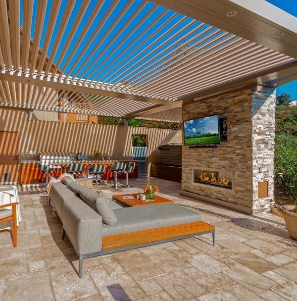 Beautiful stone paver patio with stacked stone outdoor fireplace with mounted T under opened beige pivoting pergola louvers