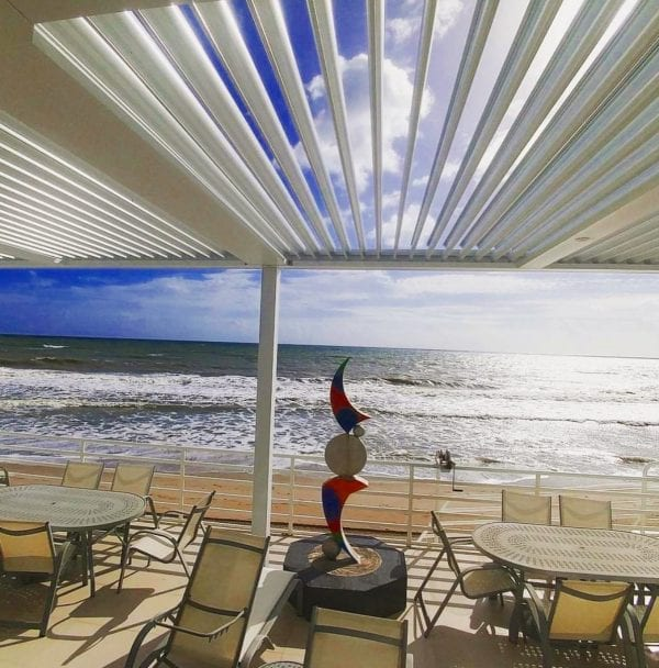 Beachside commercial patio with oval tables and tan chairs and sculpture covered by pivoting louvered shade structure