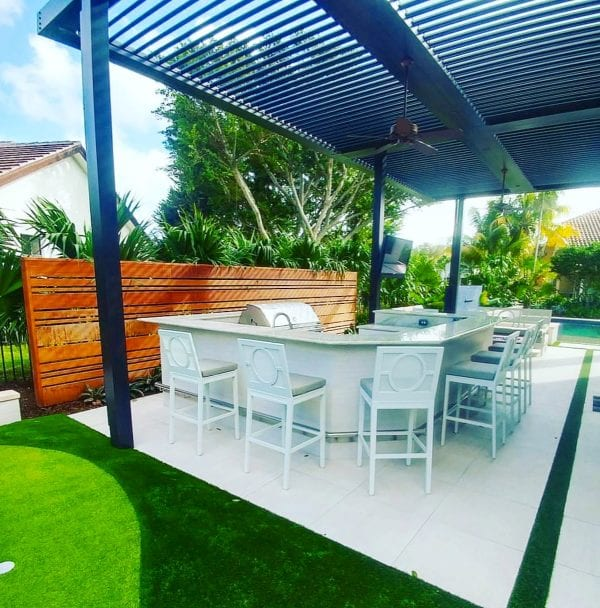 White chairs with cushions around white outdoor kitchen counter with green turf wooden horizontal slat fence under black pergola with louvers open