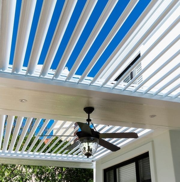 Close-up white opened pergola louvers with fan/light figure and blue sky showing through