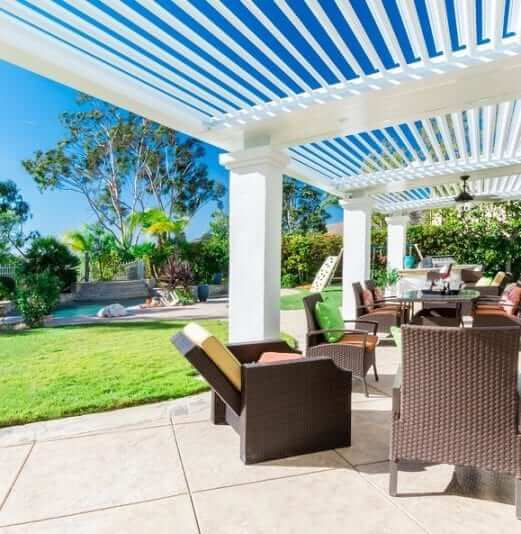White pergola on thick columns with louvers open to see blue sky with patio furniture below