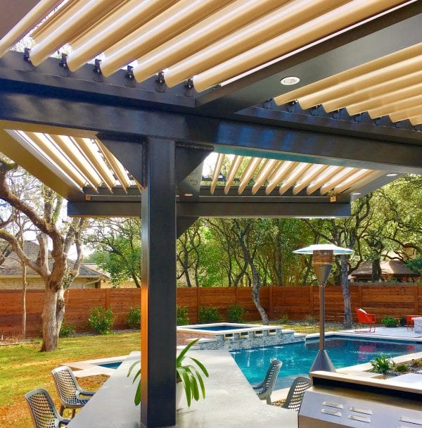 Under black and beige pivoting roof pergola with stand-up outdoor heater and pool in distance