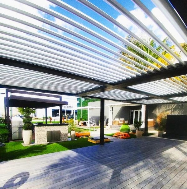 Under black pergola with white pivoting louvers open to reveal sky and palms beyond