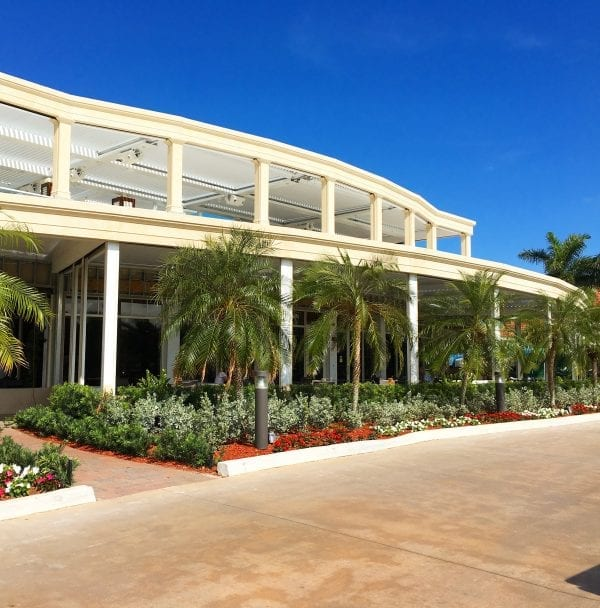 Standing on driveway looking at two-story building with second-level patio pergola visible with perfect blue sky above and small palms lining entry
