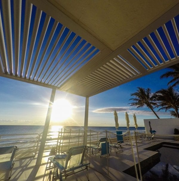 Sun setting on blue ocean as seen from patio covered by pergola