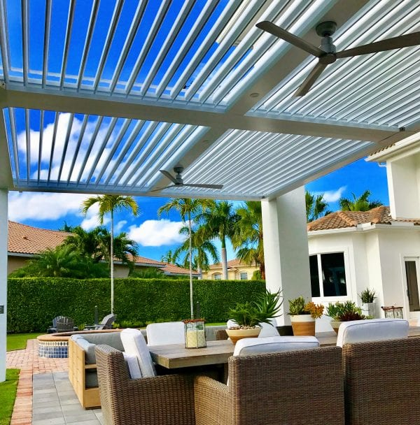 White louvered roof pergola with two fans on vibrant blue sky day with palm trees and outdoor dining furniture on patio pavers