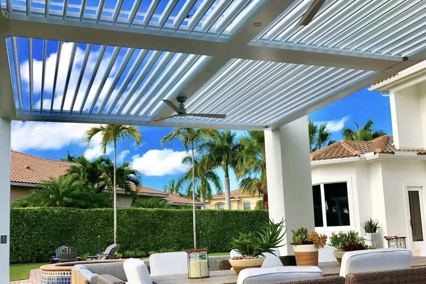 White pergola with metal louvers pivoted open over white cushioned dining chairs with plants on table and palm trees in distance