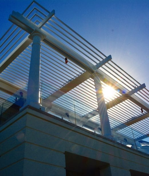 Sun shining through opened pergola louvers with blue sky in background