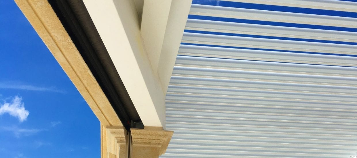 Vibrant blue sky with scatter white clouds seen through open pergola louvers