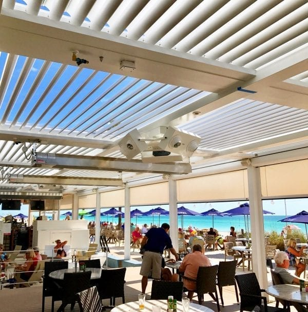 Round dining tables on patio under white pergola with heaters and screens and a row of royal blue umbrellas beyond