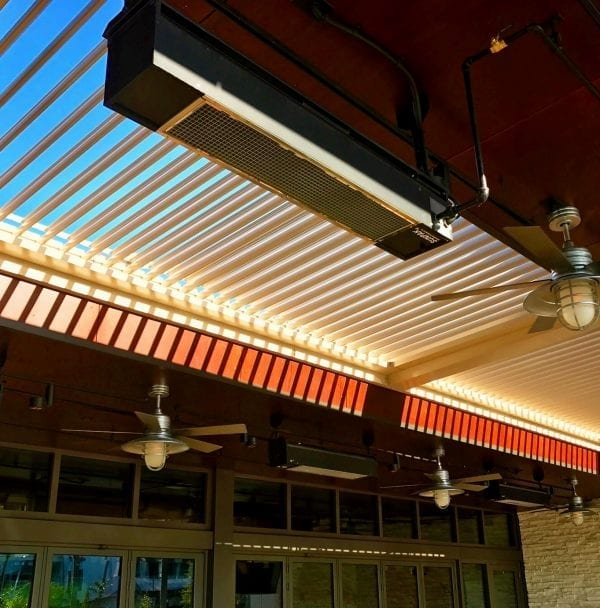Close-up heater attached to beam of pergola system with sun shining on louvers casting shadows on opposite beam