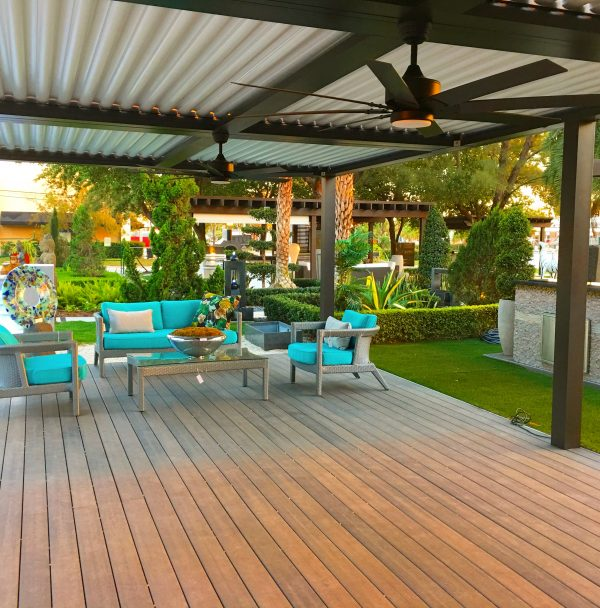 Bright turquoise cushions on outdoor seating ensemble on wooden deck under bronze pergola with white pivoting louvers
