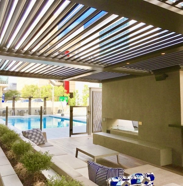 Standing under adobe louvered roof pergola with down lights over outdoor sofa facing fireplace with pool turquoise pool beyond