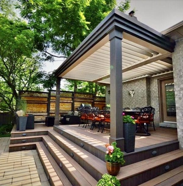 Four step-up deck with long dining table surrounded by orange seat black chairs all under bronze pergola with tan louvers