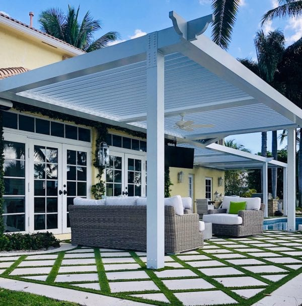 White pergola over diamond-shaped pavers with grass in-between next to yellow house with pool in background