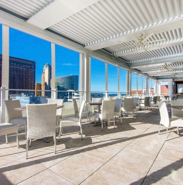 Commercial high-rise beige stone terrace with white wicker seating under white pivoting roof pergola with skyline and blue sky in background