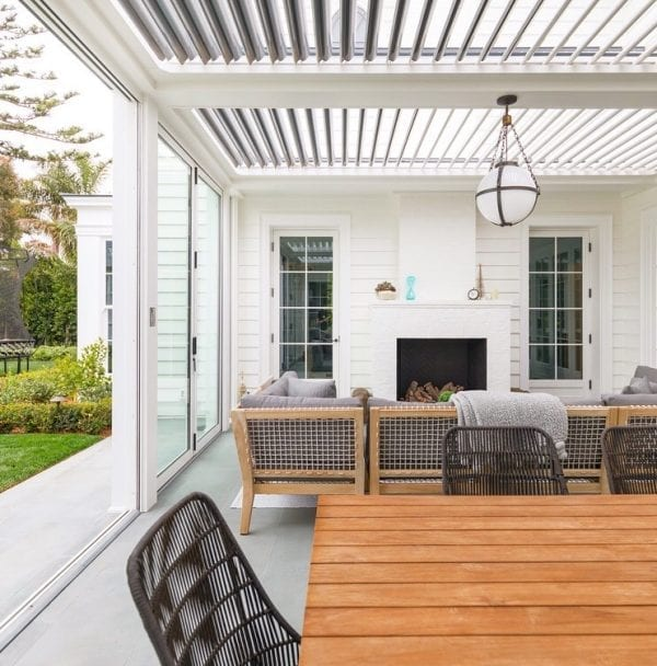 White pergola pivoting louvers over indoor outdoor patio with sliding glass walls