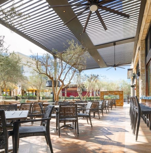 Commercial dining patio with bronze woven chairs at wooden tables under large bronze louvered pergola system with fans