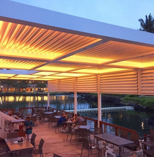 Track lighting in commercial pergola makes it glow golden at dusk