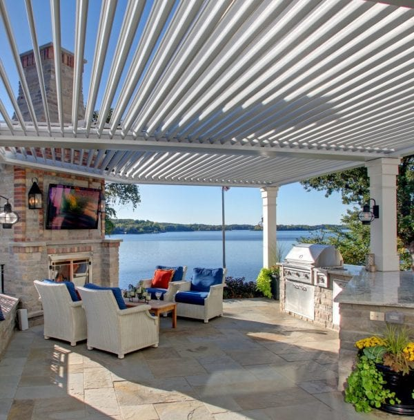 Waterside patio with white pergola louvers opened over outdoor kitchen and red white and blue seating