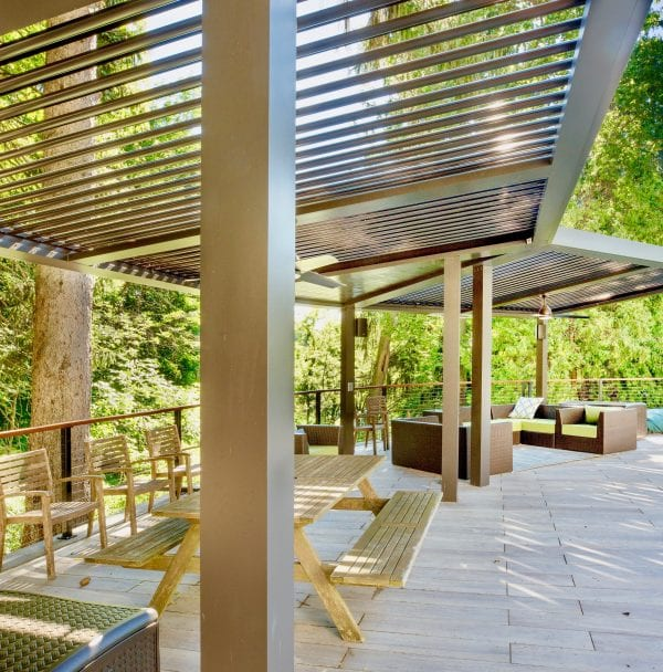 Brightened Adobe-colored Pergola X along edge of fenced patio with picnic table and other seating beneath