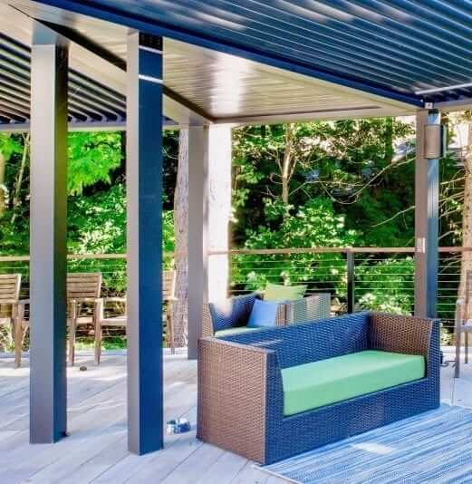 Alt close-up under closed pivoting louver pergola with pan wedge ceiling and green cushioned outdoor sofa