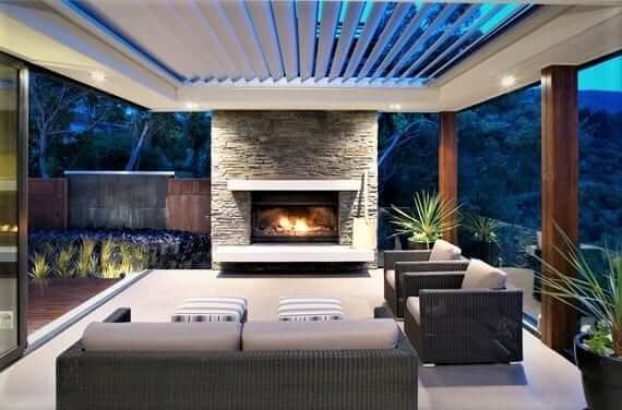 White automated pivoting louvers on wood clad posts with outdoor lounge seating facing stacked stone fireplace