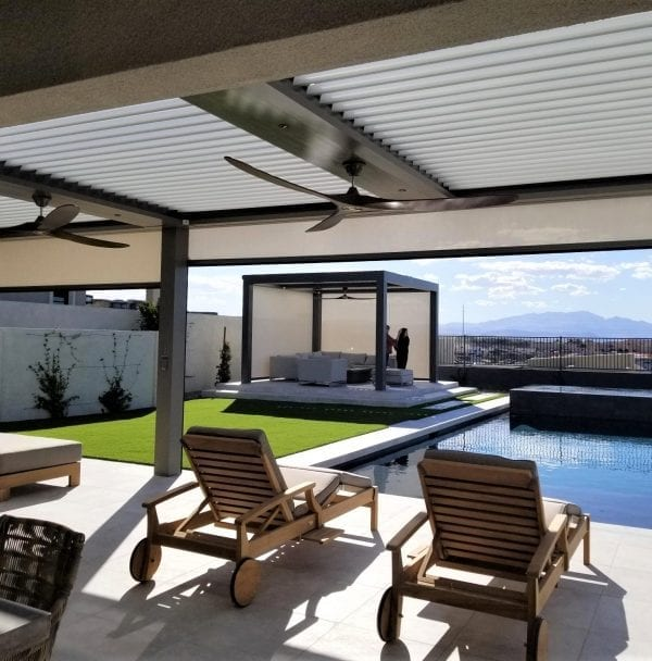 Cabana style pergola in background with seating at far end of pool and closer pergola with pivoting louvers closed and fans in foreground