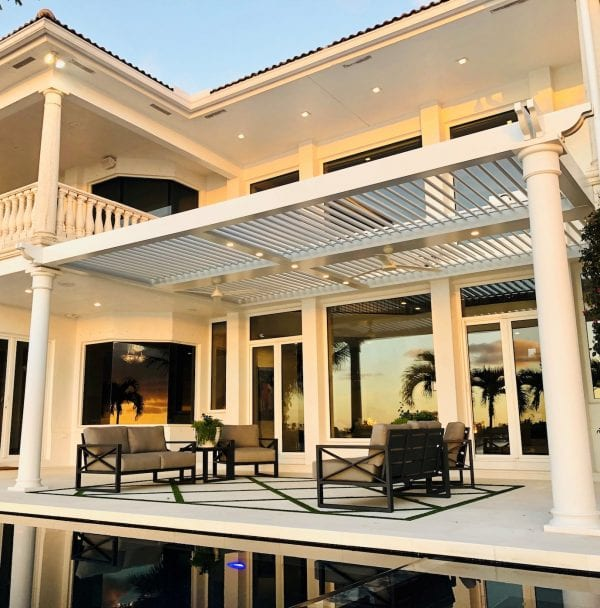 Sunset glow on white house with large windows and white pergola covering outdoor patio with gray and black furniture