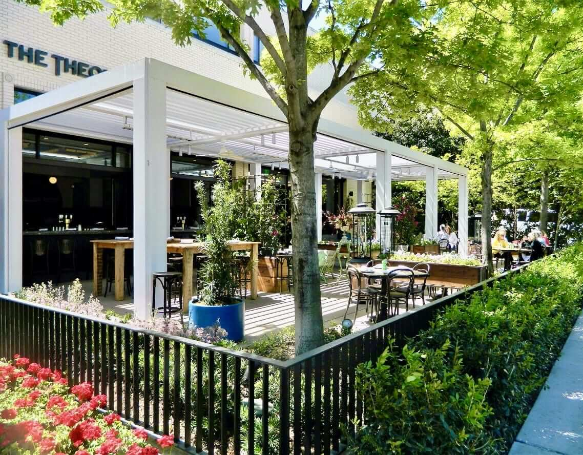 Commercial outdoor patio in garden-like setting with white pergola