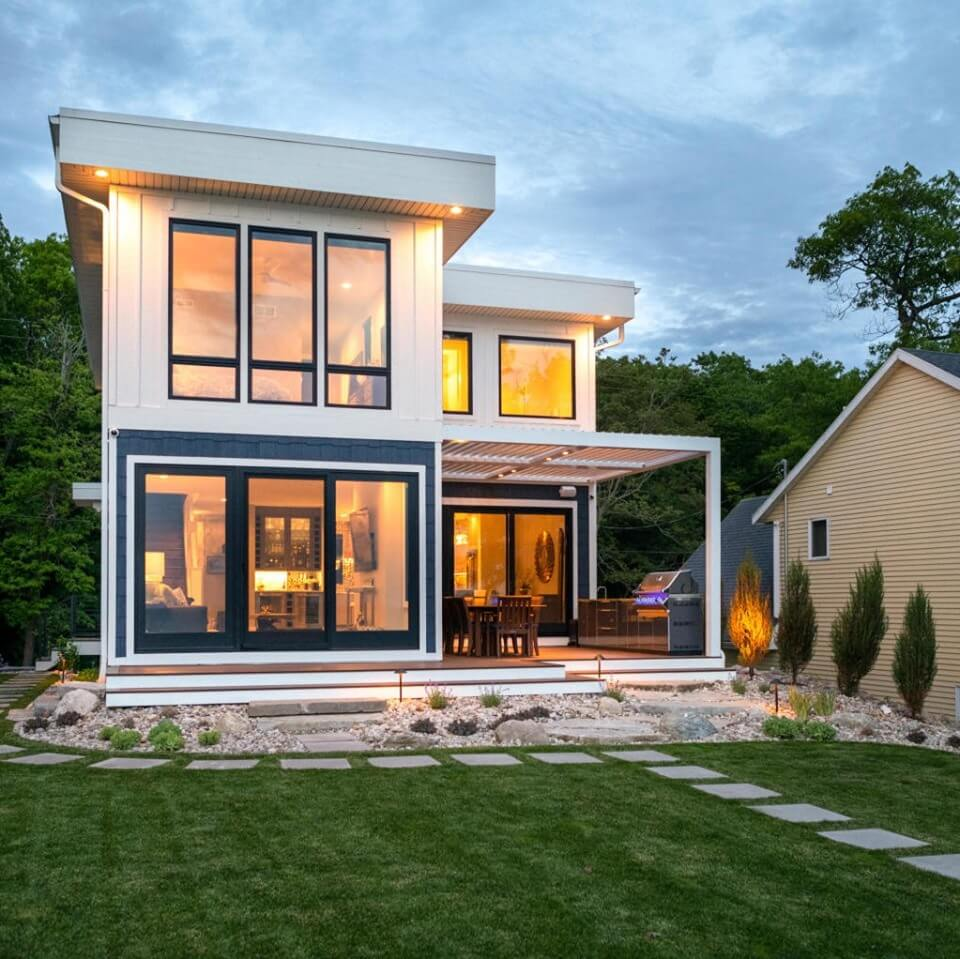 Perfect white two-story modern home with black window trim and white louvered-roof pergola with golden light shining through windows at dusk