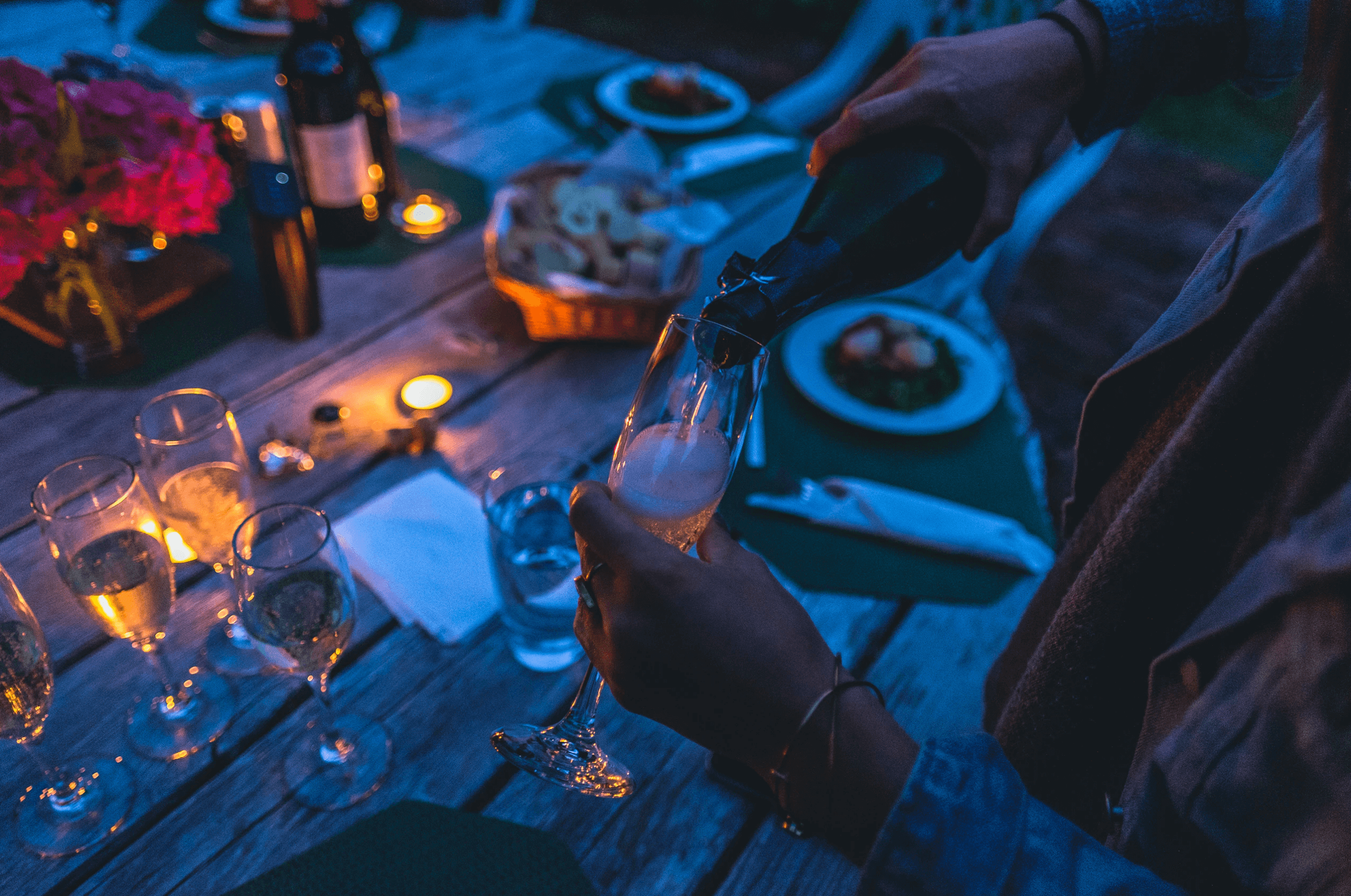 Enhanced dark outdoor round wood slat table with champagne glasses and flood and tea light with hands pouring champagne in glass