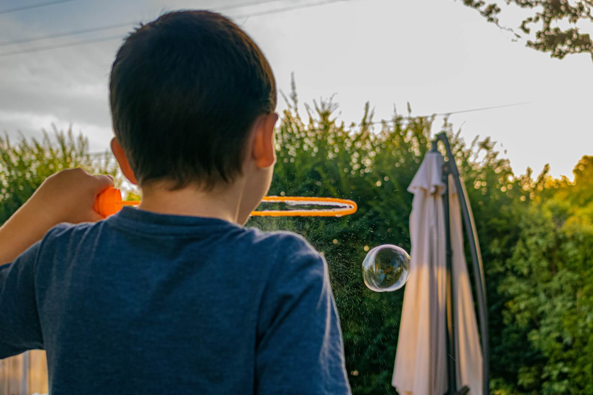 Back of boy in blue shirt of blowing bubbles through giant orange bubble ring in backyard with blurred closed umbrella beyond