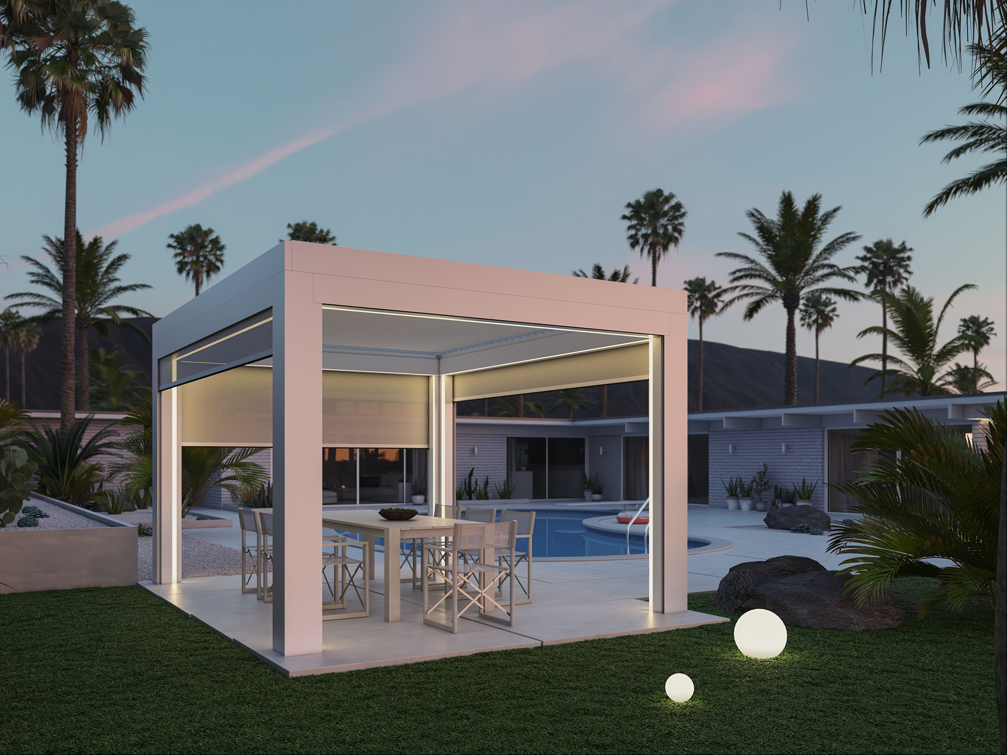 Free-standing white pergola with TraX lighting and screens over stone patio with dining table and glowing globe lights on grass
